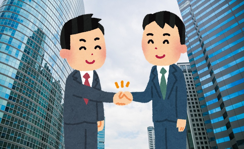 経営統合で握手する男性